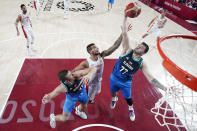 Slovenia's Luka Doncic (77) and Vlatko Cancar, left, fight for a rebound with Spain's Willy Hernangomez, center, during a men's basketball preliminary round game at the 2020 Summer Olympics, Sunday, Aug. 1, 2021, in Saitama, Japan. (Charlie Neibergall/Pool Photo via AP)