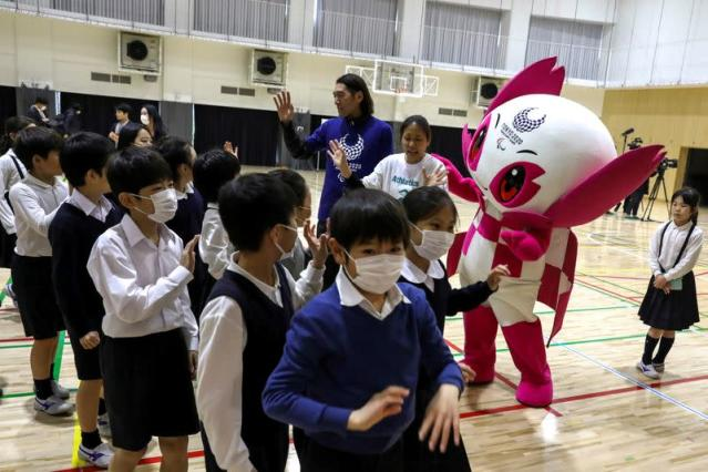 FILE PHOTO: Students of Ariake-nishi Gakuen School wear protective face masks, following the outbreak of the coronavirus, as they wave to a para-athlete Chiaki Takada and Mascot Someity after an event Six Months to go until Tokyo 2020 Paralympic Games in T