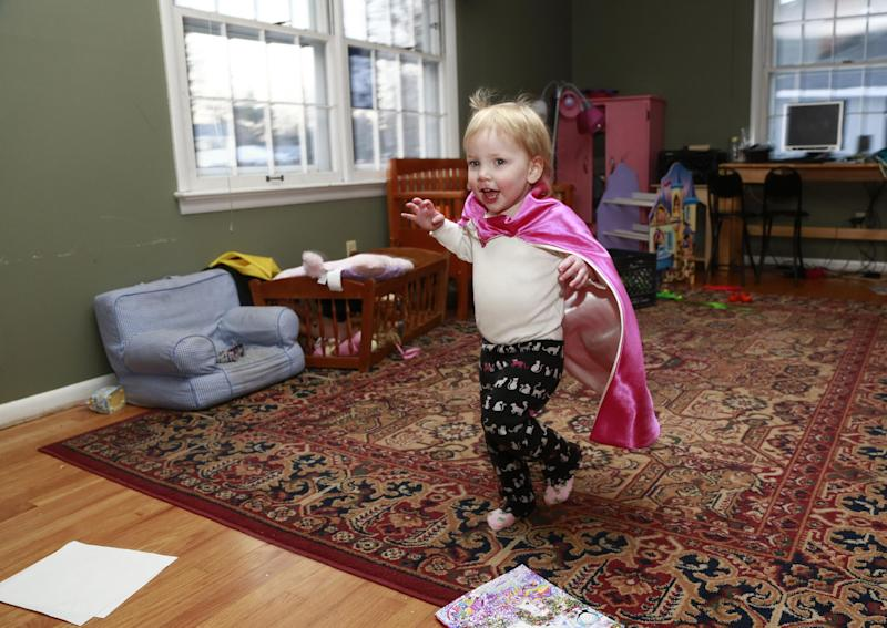 Felicity Beck-Kehoe runs wearing a cape through the family home of her parents Mike Beck and Joanne Kehoe as the family tries to combat cabin fever, Monday, Feb. 3, 2014, in Indianapolis. (AP Photo/R Brent Smith)