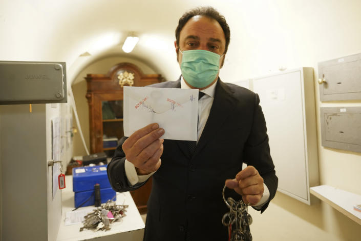 """Gianni Crea, the Vatican Museums chief """"Clavigero"""" key- keeper, shows the sealed envelope where the 19th century key of the Sistine Chapel is kept, in the a safe where the museum's keys are kept, as he prepares to open it, at the Vatican, Monday, Feb. 1, 2021. Crea is the """"clavigero"""" of the Vatican Museums, the chief key-keeper whose job begins each morning at 5 a.m., opening the doors and turning on the lights through 7 kilometers of one of the world's greatest collections of art and antiquities. The Associated Press followed Crea on his rounds the first day the museum reopened to the public, joining him in the underground """"bunker"""" where the 2,797 keys to the Vatican treasures are kept in wall safes overnight. (AP Photo/Andrew Medichini)"""