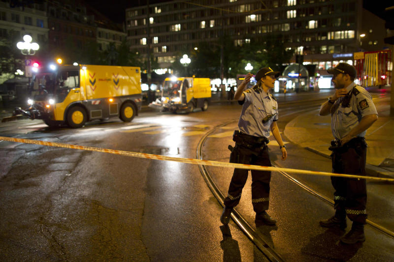 "FILE- Police officers secure the area as road sweeping vehicles clear glass near the site of Friday's explosion in Oslo, Norway, in this file photo dated Saturday, July 23, 2011. A homegrown terrorist set off the explosion that ripped open buildings in the heart of Norway's government, then went to a summer camp dressed as a police officer and gunned down dozens of youths at a Norwegian summer camp. It is announced Friday March 30, 2012, that a loosely knit group of xenophobic ""defense leagues"" plans to rally in Denmark upcoming Saturday against what they call the growing Islamic presence in western Europe, with fears across Europe that a growing climate of ethnic and religious hostility is inspiring extremist violence, and creating the conditions for deadly unpredictable clashes. (AP Photo/Matt Dunham, FILE)"