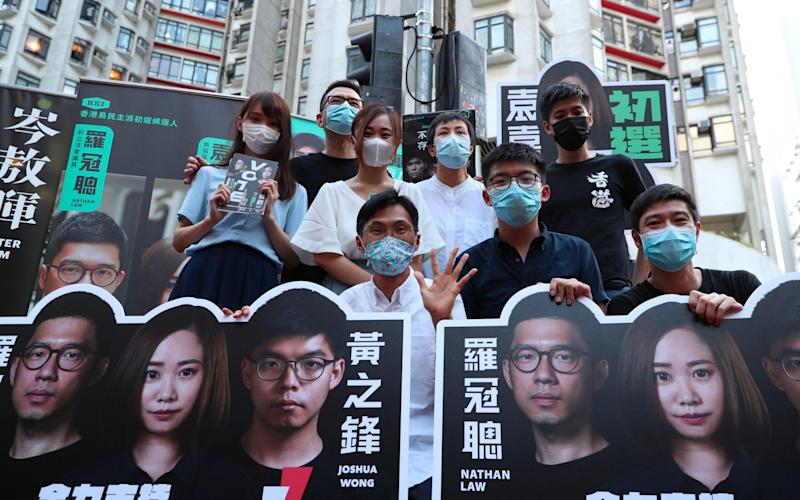 Joshua Wong, second from left front row, poses with other pro-democracy activists while campaigning for the primary - AFP