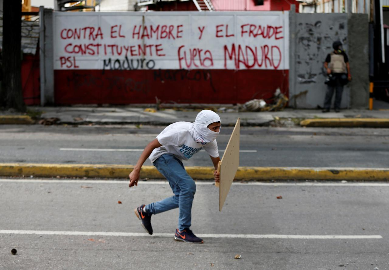 """A demonstrator walks during clashes with riot security forces at a rally against Venezuela's President Nicolas Maduro's government in Caracas, Venezuela, July 28, 2017. The graffiti on the wall reads: """"Against the hunger and the constituent fraud"""" and """"Maduro leave"""".  REUTERS/Andres Martinez Casares"""