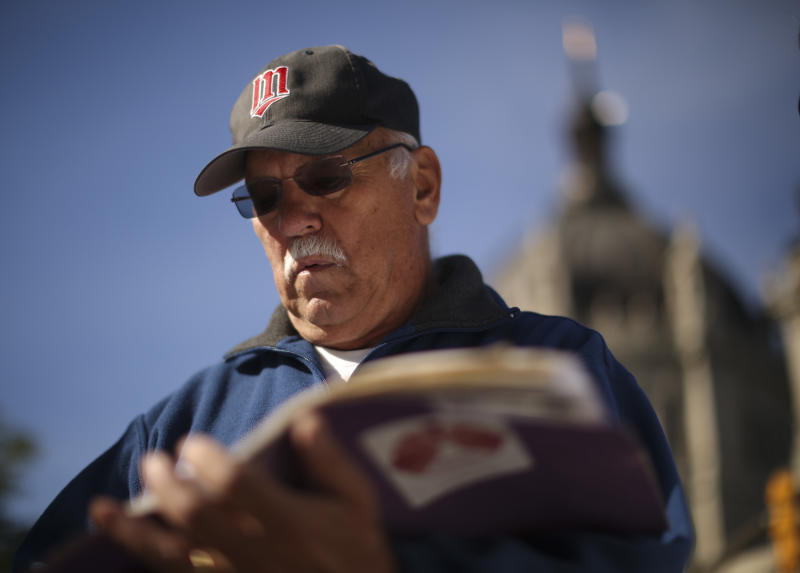 Frank Meuers looks through a folder than contains all his information and correspondence with the Archdiocese, outside the headquarters of the Catholic Church in St. Paul, Minn. Monday afternoon, Oct. 7, 2013 after a news conference presented by SNAP, Survivors Network of those Abused by Priests. Meuers came forward and for the first time publicly told how he was abused by a priest, Rudolph Henrich, while a youngster in Golden Valley. (AP Photo/The Star Tribune, Jeff Wheeler) MANDATORY CREDIT; ST. PAUL PIONEER PRESS OUT; MAGS OUT; TWIN CITIES TV OUT