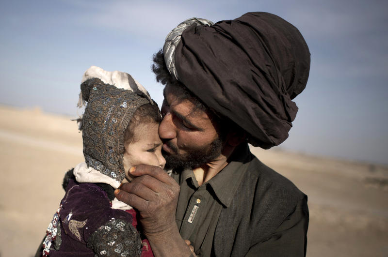 In this Oct. 20, 2012 photo, an Afghan nomad kisses his young daughter while watching his herd in Marjah, Helmand province, Afghanistan. In southern Helmand province, one of Afghanistan's deadliest battlefields, angry residents say 11 years of war has brought them widespread insecurity. They say they are too afraid to go out after dark because of marauding bands of thieves and during the day corrupt police and government officials bully them into paying bribes. Development that was promised hasn't materialized and the Taliban's rule is often said to be preferred. (AP Photo/Anja Niedringhaus)