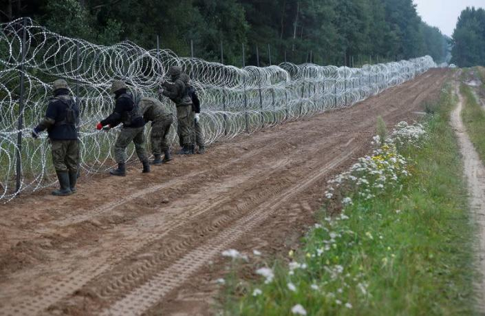 FILE PHOTO: Polish soldiers build a fence on the border between Poland and Belarus near the village of Nomiki