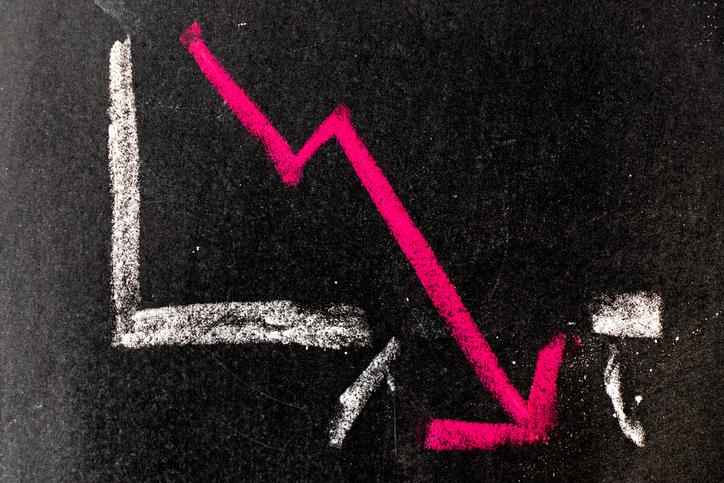 A pink arrow on a trendline smashing through the bottom axis on a chart written in white chalk on a blackboard.