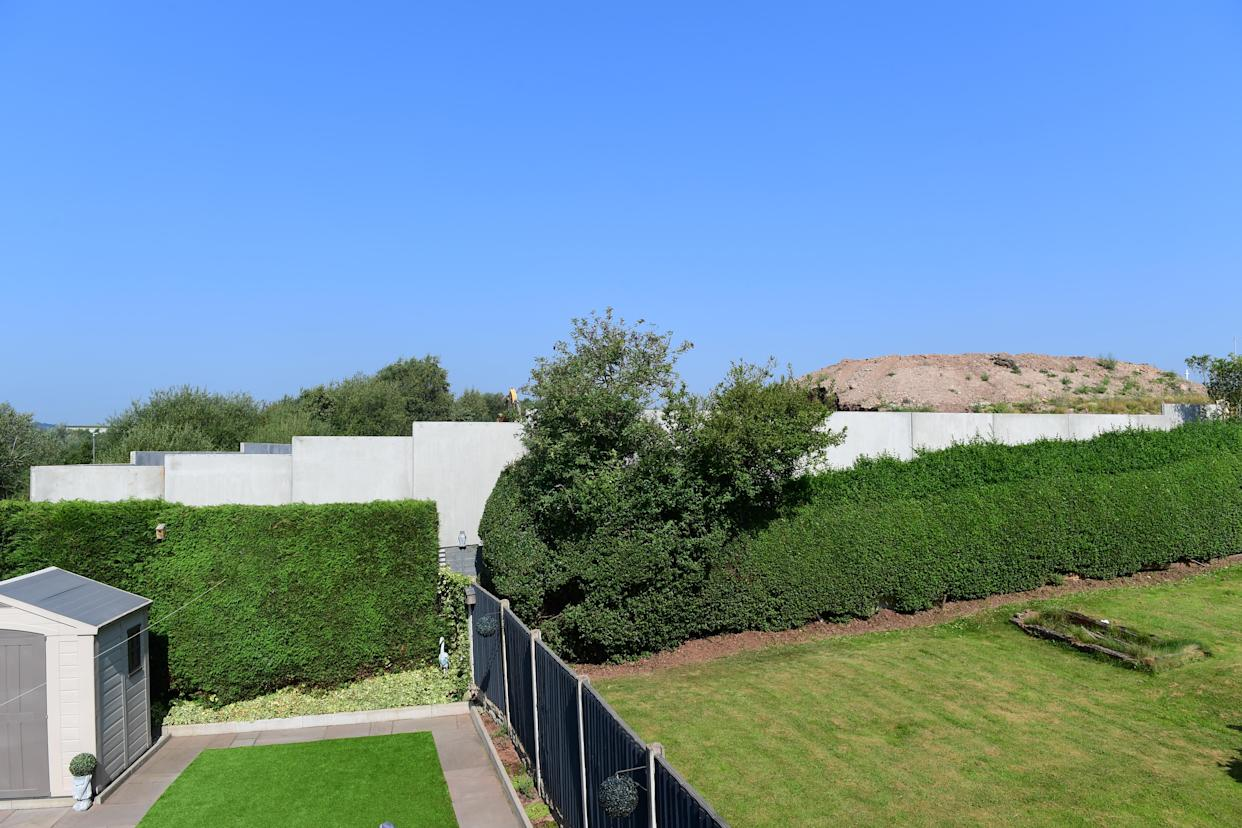 The developer has offered to pay for trees to cover the wall. (Reach)