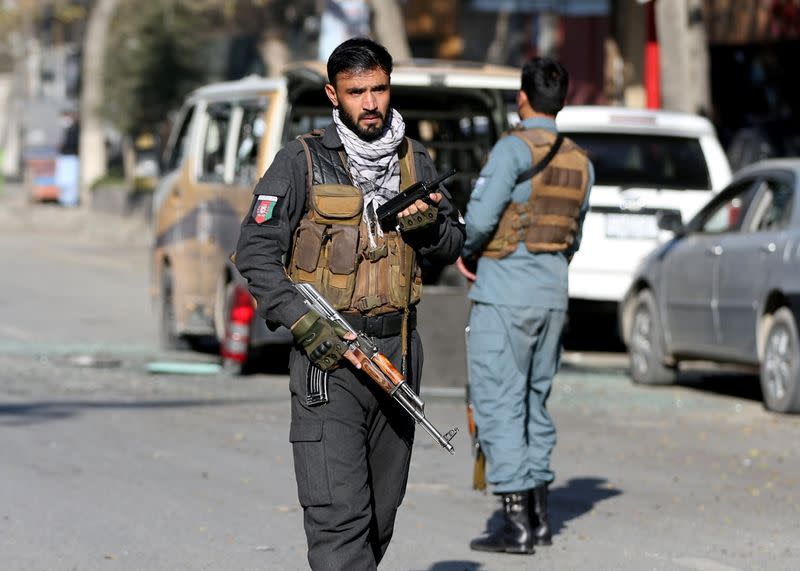 A police officer stands guard after rockets hit residential areas in Kabul