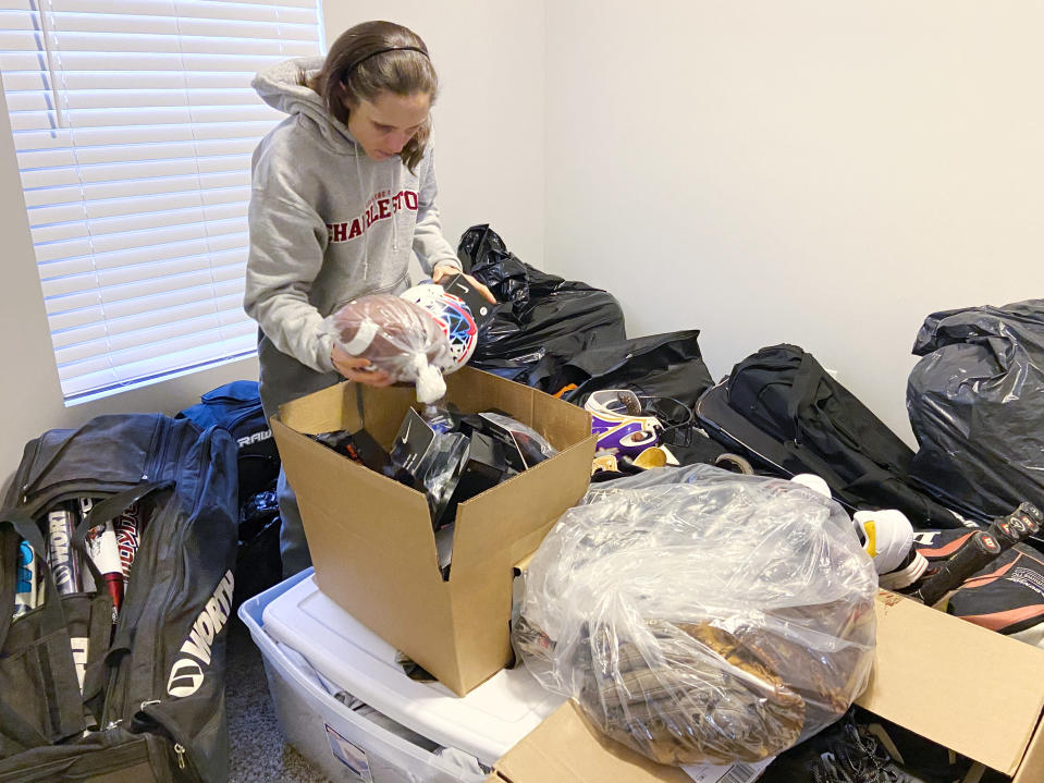 Rhiannon Potkey sorts sports equipment Jan. 30, 2021, in Knoxville, Tenn. Goods4Greatness, the nonprofit started by Potkey, works to get much-needed gear to low-income children and teens to make sure the high cost of equipment doesn't stop their athletic dreams. (AP Photo/Teresa Walker)