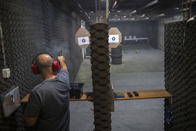 A member of Rio de Janeiro's Colt 45 Shooting Club lets off some rounds at the club's firing range (AFP Photo/Mauro Pimentel)