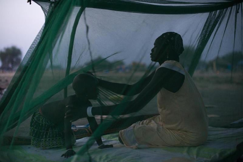 A mother and child take cover under a mosquito net at a site for internally displaced persons in Minkamen, South Sudan (AFP Photo/Phil Moore)
