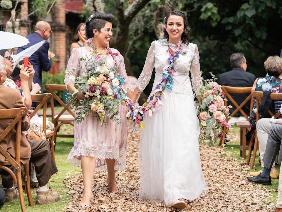 Two brides hold hands as they leave their wedding ceremony.