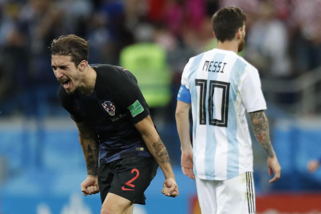 Argentina's Lionel Messi, right, leaves the pitch as Croatia's Sime Vrsaljko celebrates his side's 3-0 victory at the end of the group D match between Argentina and Croatia at the 2018 soccer World Cup in Nizhny Novgorod Stadium in Novgorod, Russia, Thursday, June 21, 2018. (AP Photo/Pavel Golovkin)