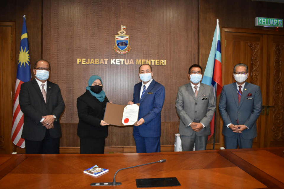 Datuk Seri Hajiji Noor (2nd right) handing over a letter of appointment to incoming Kota Kinabalu mayor Noorliza Awang Alip. — Picture courtesy of Chief Minister's Department