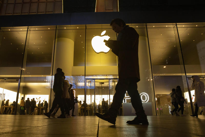 FILE - In this Dec. 13, 2019, file photo a man looks at his phone as he walks past a store of US tech giant Apple in a retail district in Beijing. Apple reports financial earns on Tuesday, Jan. 28, 2020.(AP Photo/Ng Han Guan, File)