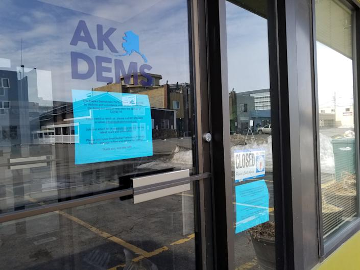 """A """"Closed"""" sign is displayed at the window of the Alaska Democratic Party headquarters in Anchorage, Alaska, U.S., April 11, 2020. (Yereth Rosen/Reuters)"""