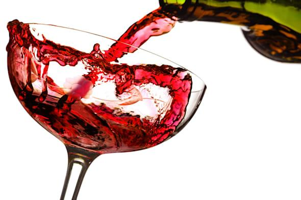 BR7WB0 Red wine pouring into a glass, studio isolated on white background