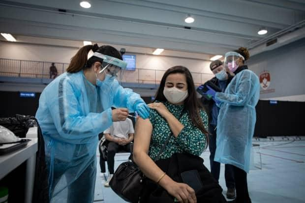 Health-care workers administer doses of the Pfizer COVID-19 vaccine at a clinic in MIssissauga earlier this month. (Evan Mitsui/CBC - image credit)