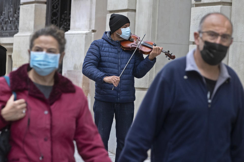 A street musician plays for passers-by in Madrid, Spain, Sunday, Nov. 15, 2020. Spain continues with new measures against the COVID-19 while suffering a second strong pandemic crisis by Coronavirus. (AP Photo/Paul White)