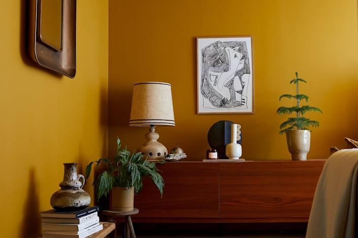 Other elements in the cozy living room include a wall illustration by Atelier CPH above a modular sideboard from Habitat, on which sits a Muse Clio white ceramic vase fromFerm Living and a vintage lamp the couple picked up in Dusseldorf, Germany.