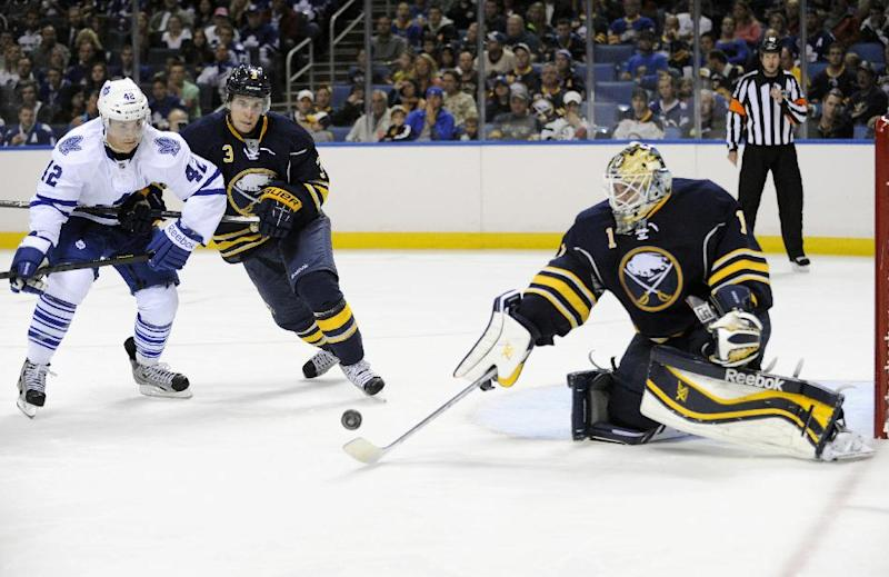 Toronto Maple Leafs' Tyler Bozak (42) and Buffalo Sabres' Mark Pysyk (3) watch as Sabres' Jhonas Enroth (1) knocks the puck away during the second period of an NHL hockey preseason game in Buffalo, N.Y., Saturday, Sept. 21, 2013. (AP Photo/Gary Wiepert)