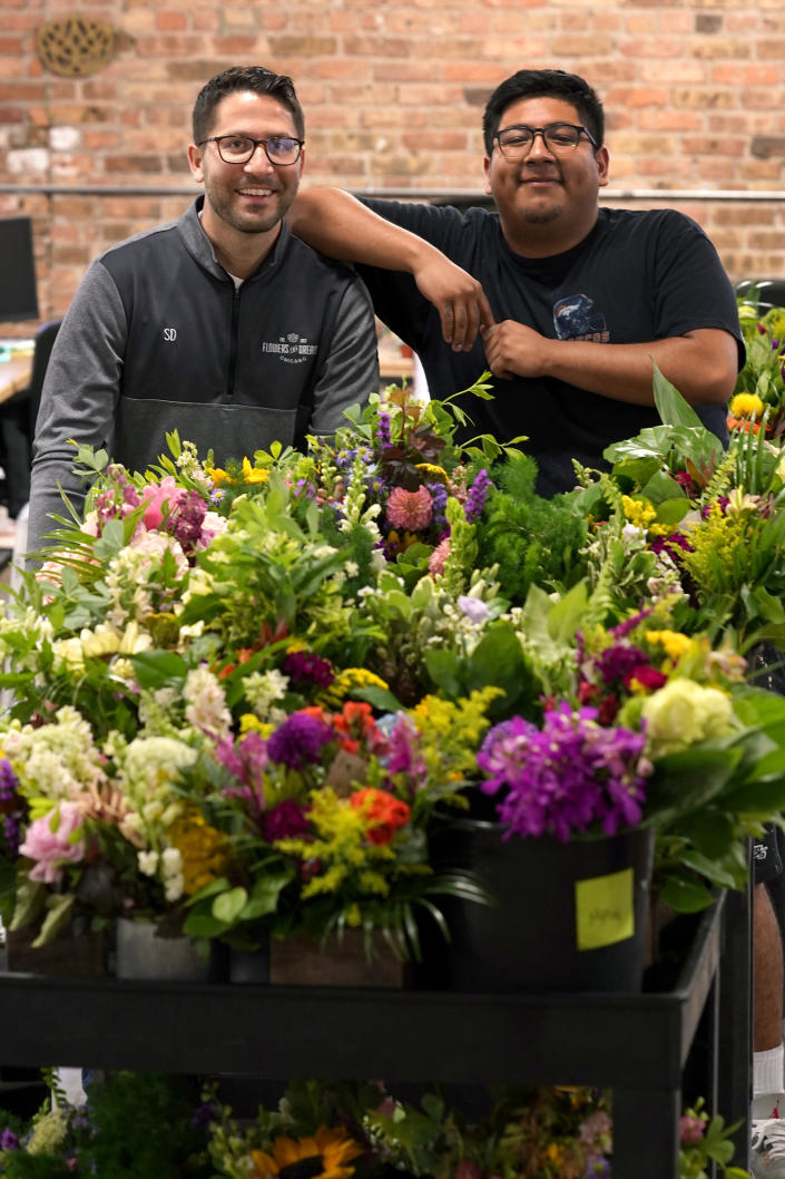 Steven Dyme, owner of Flowers for Dreams, poses with employee Kevin Cervantes for a portrait at the company's warehouse Friday, July 23, 2021, in Chicago. Dyme says the $15 minimum made it much easier to staff up when the economy reopened this spring and demand for flowers, particularly for weddings, soared. The company has four locations, including its headquarters in Chicago, one in Milwaukee, and two in Detroit. (AP Photo/Charles Rex Arbogast)