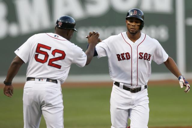 Boston Red Sox's Xander Bogaerts celebrates his solo home run with third base coach Carlos Febles (52) during the first inning of the team's baseball game against the Toronto Blue Jays in Boston, Tuesday, July 16, 2019. (AP Photo/Michael Dwyer)