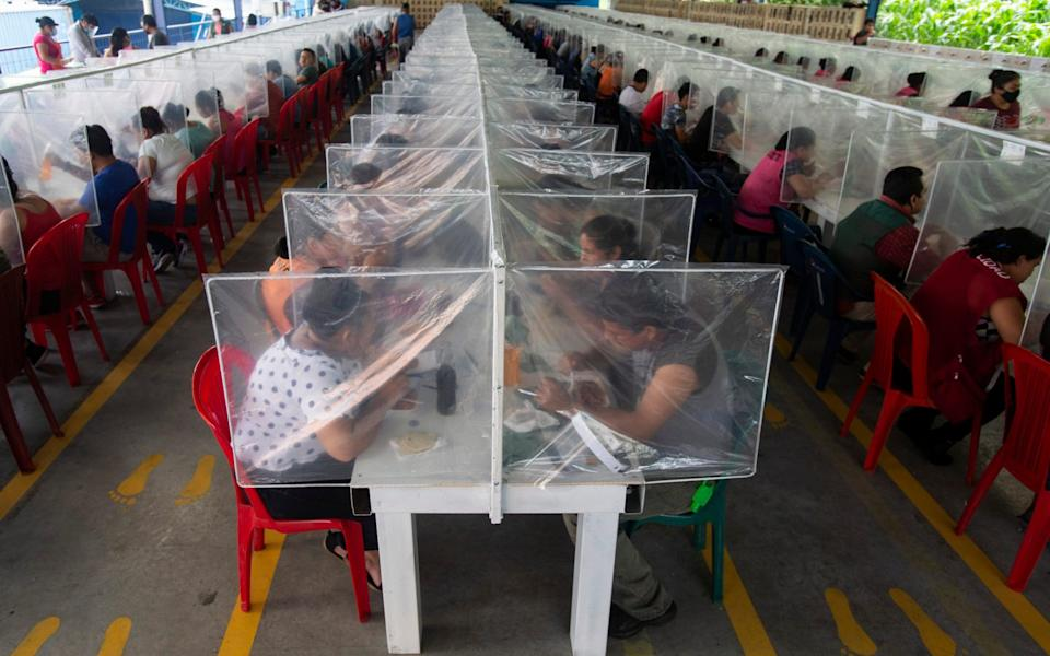 Workers eat their lunch separated by plastic panels as a measure against the spread of the new coronavirus at the Korean-owned firm K.P. Textil - employees returned to work this weekend after more than a month-long quarantine - AP Photo/Moises Castillo