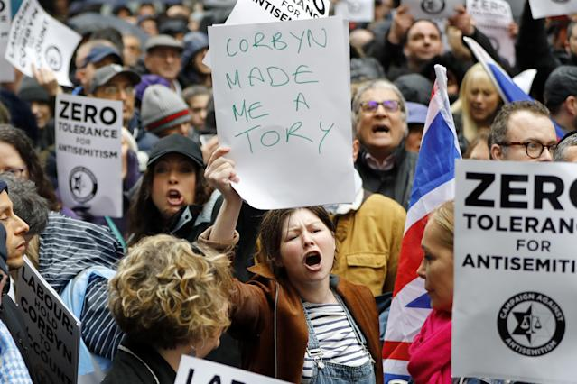 "A woman holds up a placard declaring ""Corbyn made me a Tory"" as she joins protesters gathering for a demonstration organised by the Campaign Against Anti-Semitism outside the head office of the British opposition Labour Party in central London on April 8, 2018. (Photo: Tolga Akmen/AFP/Getty Images)"