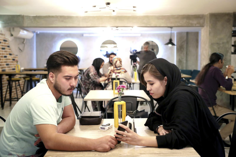 """In this Monday, Oct. 7, 2019 photo, two Afghan refugees spend time at an Afghan cafe in downtown Tehran, Iran. More than 3 million Afghans including as many as 2 million who entered without legal permission, live in the Islamic Republic, according to United Nations estimates. Fatemeh Jafari, a 21-year-old Afghan refugee, hopes her Telma, or """"Dream,"""" Café in Tehran will help bridge the divides and xenophobia Afghans can face in Iran. (AP Photo/Ebrahim Noroozi)"""
