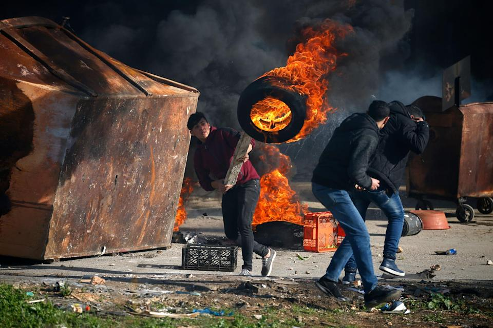 A Palestinian uses a piece of wood to move a burning tire during clashes with Israeli troops in Ramallah, near the settlement of Beit El, in the occupied West Bank: ABBAS MOMANI/AFP/Getty Images