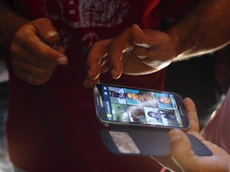 Syrian refugees look at photos of their missing and believed to have drowned compatriots on a smartphone at the Hal Far open centre for migrants in Hal Far