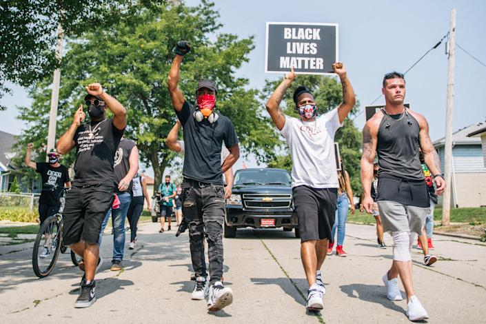 Demonstrators participate in a march on August 24, 2020 in Kenosha, Wisconsin. A night of civil unrest occurred after the shooting of Jacob Blake, 29, on August 23. Blake was shot multiple times in the back by Wisconsin police officers after attempting to enter into the drivers side of a vehicle.
