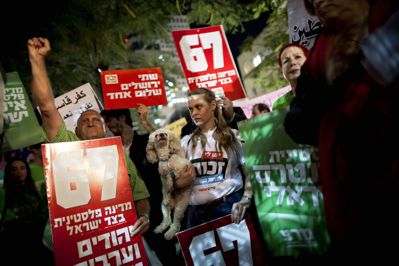 "Israeli left wing activists support the Palestinian U.N. bid for observer state status, during a rally in Tel Aviv, Israel, Thursday, Nov. 29, 2012. The Palestinians are certain to win U.N. recognition as a state on Thursday but success could exact a high price: delaying an independent state of Palestine because of Israel's vehement opposition. Hebrew on sign reads: ""Jews and Arabs refuse to be enemies."" (AP Photo/Oded Balilty)"