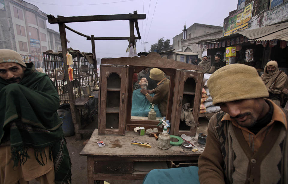 <p>A Pakistani street barber, right, gives a haircut to a customer, reflected in a mirror, in Gujranwala, near Lahore, Pakistan, Jan. 6, 2011. (Photo: Muhammed Muheisen/AP) </p>