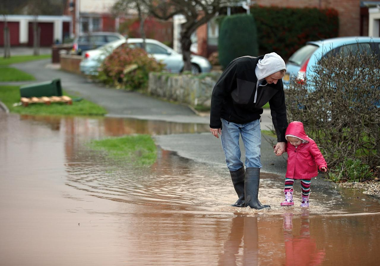 TAUNTON, UNITED KINGDOM - NOVEMBER 25:  A young girl splashes through flood water in the centre of the village of Ruishton, near Taunton, on November 25, 2012 in Somerset, England. Another band of heavy rain and wind continued to bring disruption to many parts of the country today particularly in the south west which was already suffering from flooding earlier in the week.  (Photo by Matt Cardy/Getty Images)