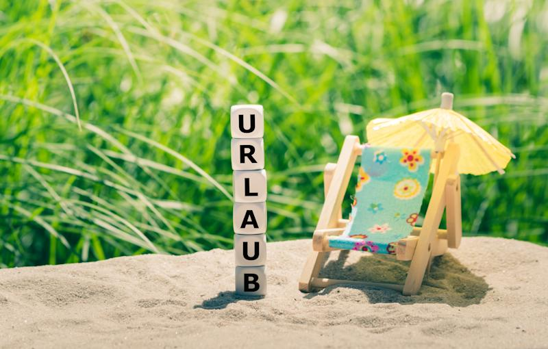 "Dice form the German word ""URLAUB"" (""holiday"" in English) next to a beach chair."