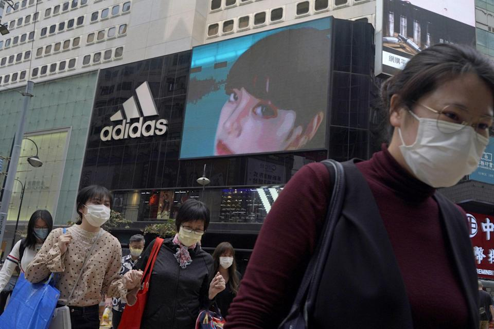 People walk past an Adidas sportswear store in Hong Kong, Saturday, March 27, 2021. Chinese textile and apparel makers are profiting from Chinese boycott of foreign brands. Photo: AP