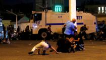 FILE PHOTO: People take cover near policemen as gunfire are heard during an attempted coup in Istanbul's Taksim Square