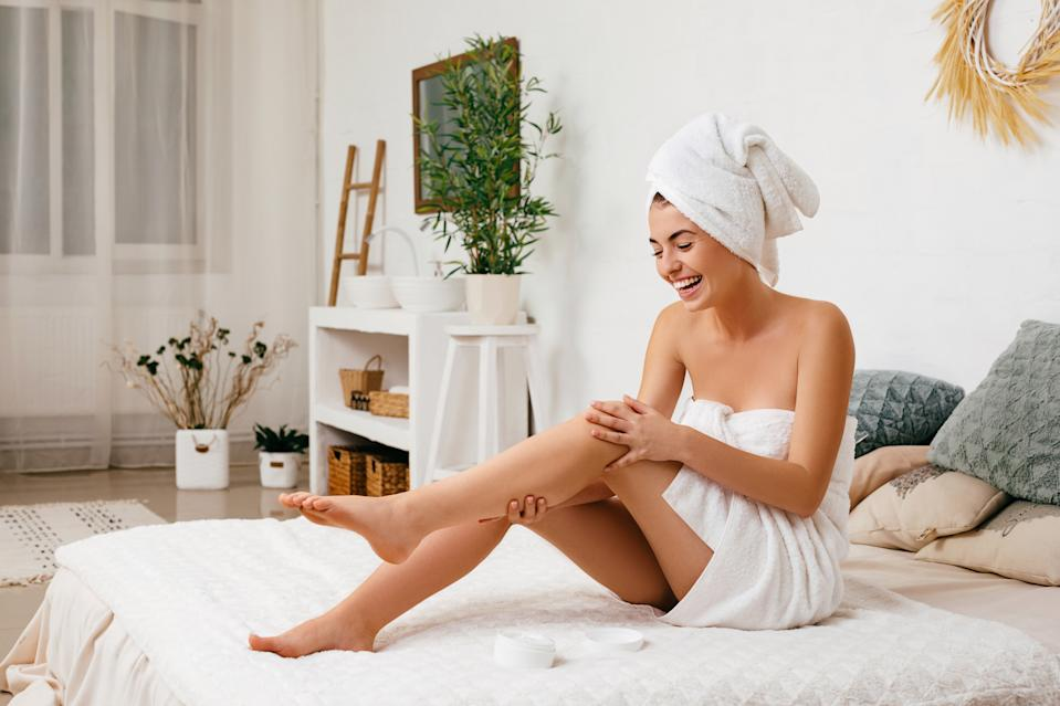 Young beautiful woman in towel applying cream on her legs after shower at home
