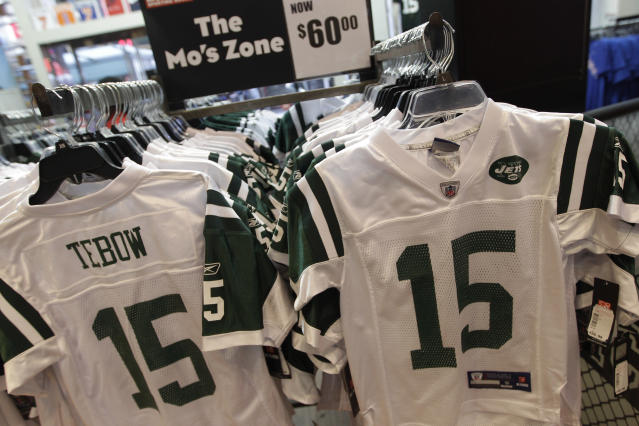 New York Jets football jerseys with the name and number of their new quarterback Tim Tebow hang on display at a Modell's store, Monday, March 26, 2012, in New York. At his introductory news conference Monday, the New York Jets backup quarterback, acquired from Denver last Wednesday, says he's grateful and excited to be with the team. (AP Photo/Mary Altaffer)