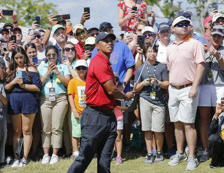 Mar 18, 2018; Orlando, FL, USA; After taking relief, Tiger Woods hits his second shot to the green on the ninth hole during the final round of the Arnold Palmer Invitational golf tournament at Bay Hill Club & Lodge. Reinhold Matay-USA TODAY Sports