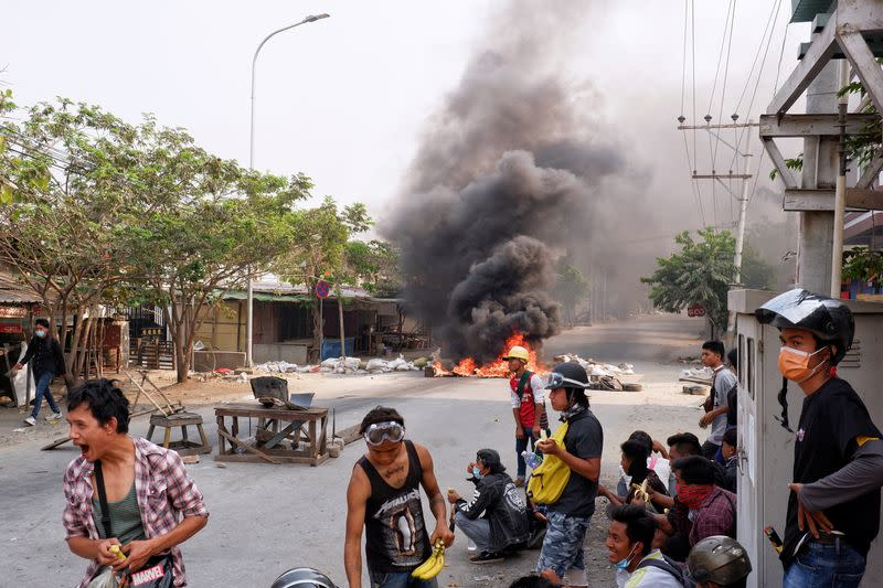 Demonstrators gather behind barricades during a protest against the military coup in Mandalay
