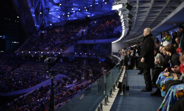 Russian President Vladimir Putin, right, stands to declare the 2014 Winter Olympics open during the opening ceremony, Friday, Feb. 7, 2014, in Sochi, Russia. (AP Photo/David Goldman, Pool)