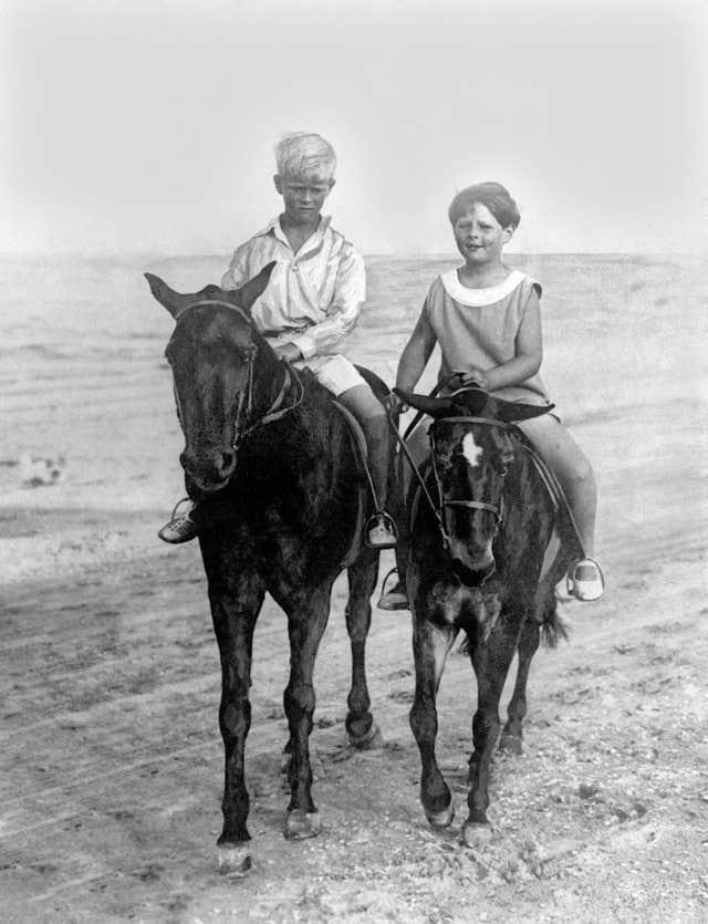 King Michael Of Romania, right, rides with his cousin Prince Philip of Greece on the sands at Constanza