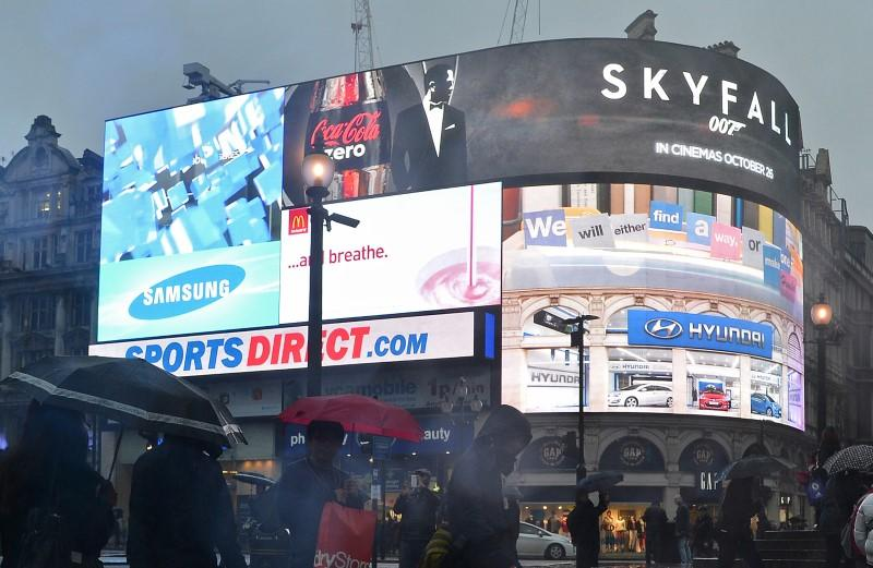 Shoppers pass an advertisement for the forthcoming James Bond film, Skyfall, on the electronic screens at Piccadilly Circus in central London