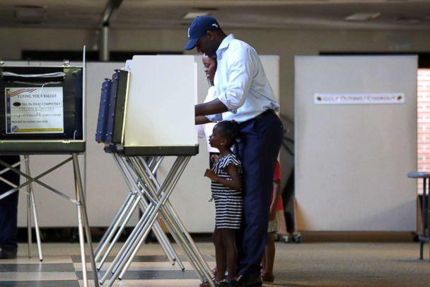 PHOTO: Florida gubernatorial candidate Andrew Gillum casts his vote, with daughter Caroline, 4, by his side at the Good Shepherd Catholic Church polling location, Aug. 28, 2018, Tallahassee, Fla. (Joe Rondone/Democrat via USA TODAY NETWORK)