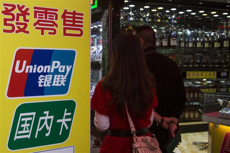 Chinese visitors walk past a sign for China UnionPay outside a pawnshop in Macau