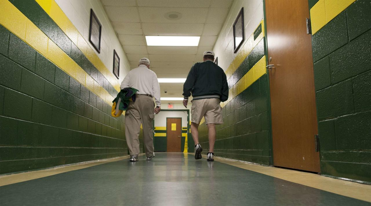 Summerville High School athletic director and head football coach John McKissick (L) and long-time friend John Kalinofski walk to a car before the start of a Friday night playoff game at Summerville High School's memorial stadium in Summerville, South Carolina on November 15, 2013. With 613 career wins under his belt, McKissick, the coach of the small-town South Carolina high school football team has blazed a victory trail unmatched at any level of the American sport. In terms of high school football, McKissick has had more career wins than any other coach in the country, a distinction he first earned in 1993. Last Friday, his team at the high school notched another playoff victory for McKissick, who after 62 seasons and 10 state championship titles has no plans to retire. Picture taken on November 15. To match story USA-SOUTHCAROLINA/COACH REUTERS/Randall Hill (UNITED STATES - Tags: SPORT FOOTBALL)